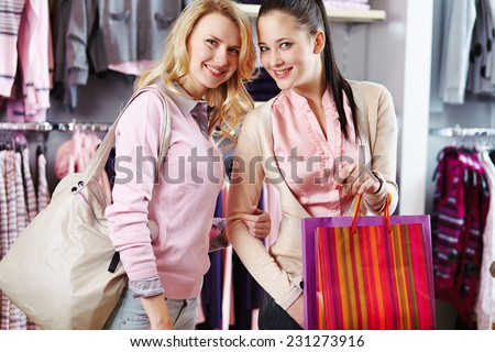 Two friendly females with shopping bags in department store - stock photo