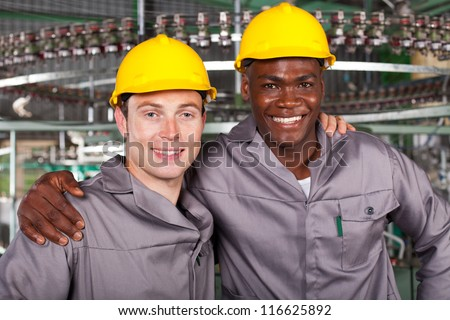 two friendly industrial workers colleagues in factory - stock photo