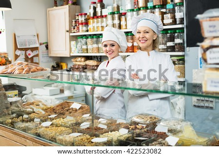 Two friendly women at confectionery display with pastry - stock photo
