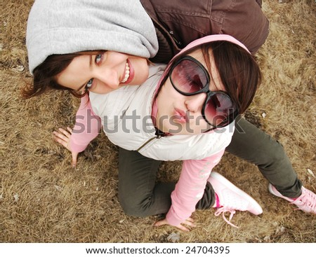 two friends are having fun on the grass - stock photo