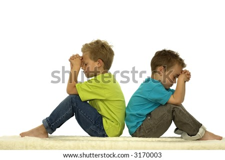 Two friends are praying while sitting with their backs against each other. - stock photo