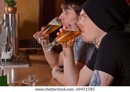Two friends are sitting in a pub and drinking a beer - stock photo