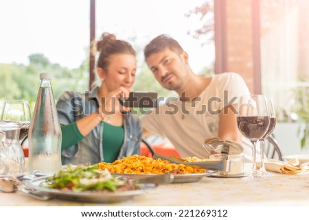 Two friends at lunch - Couple of lovers taking a self portrait at italian restaurant - stock photo