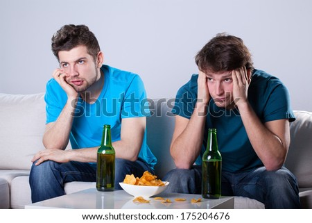 Two friends bored over bottles of beer and nachos - stock photo