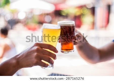 Two friends celebrating with beer. Cheers my friend! - stock photo