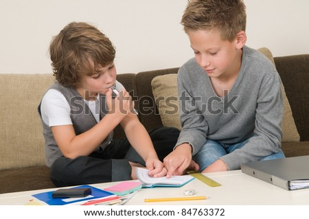 Two friends doing their homework in the livingroom - stock photo