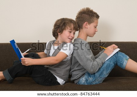 Two friends doing their homework in the livingroom on the couch - stock photo