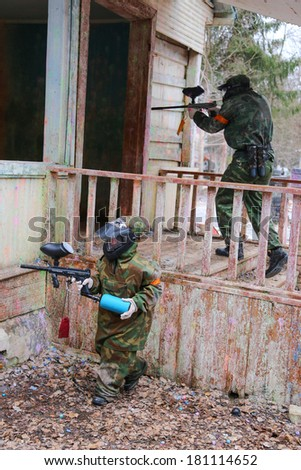 Two friends entering the building on paintball game - stock photo