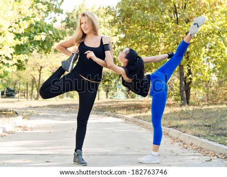 Two friends exercising together in a park doing stretching exercises to limber up their muscles before doing a training workout - stock photo