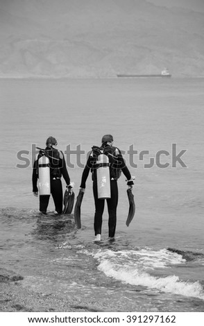 Two friends going to dive (Eialt, Israel). Coral Beach Nature Reserve in Eilat, one of the most beautiful coral reef in the world, is famous tourist and diver attraction. Aged photo. Black and white. - stock photo