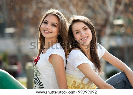 two friends, happy, young women in the park - stock photo
