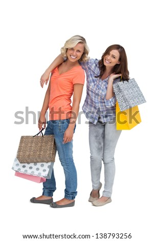 Two friends holding shopping bags on white background - stock photo