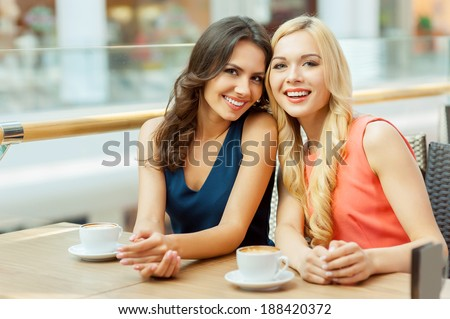 Two friends in cafe. Two young female friends sitting in cafe and looking at camera - stock photo