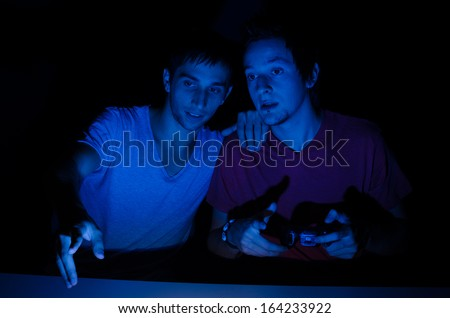 Two friends in front of a computer screen gaming - stock photo