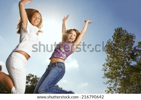 Two friends jumping in the air. - stock photo