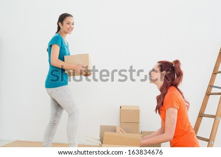 Two friends moving together in a new house and unwrapping boxes - stock photo