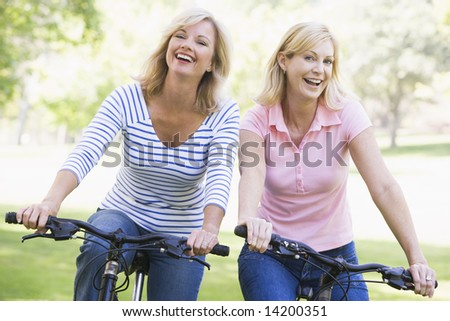 Two friends on bikes outdoors smiling - stock photo