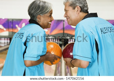 Two friends on bowling league about to bowl - stock photo
