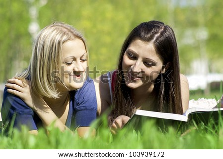 two friends on the nature of reading a book - stock photo