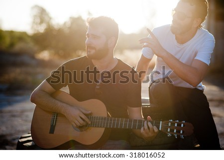 Two friends playing guitar - stock photo