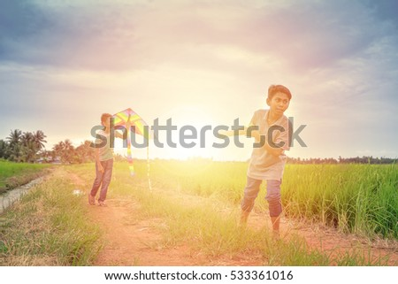 Two friends playing with kite at paddy field in the evening