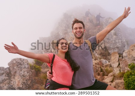 Two friends posing happily on a misty mountain top having climbed a nature trail - stock photo