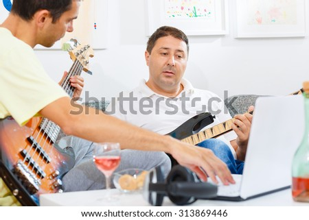 Two friends practicing their music skill with instruments and reading tabs form the computer.
