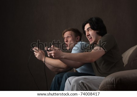 two friends pushing each other while playing video games on gray background - stock photo