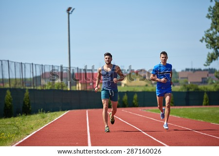 Two friends running on the lines at the stadium in a sunny day - stock photo