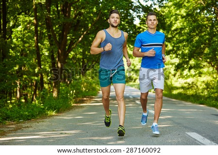 Two friends running through the forest on a jogging trail - stock photo