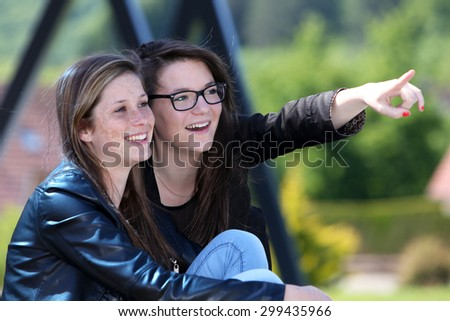 Two friends showing a direction with the hand