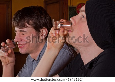 Two friends sitting in a pub and drinking hard liquor - stock photo