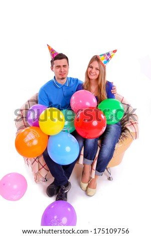 Two friends sitting on the couch with hats and balloons isolated - stock photo