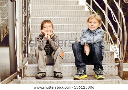 two friends sitting on the stairs - stock photo