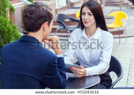 Two friends sitting outdoor in cafe thinking, looking at tablet and discussing their business. - stock photo