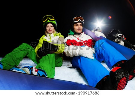 Two friends sitting with snowboards at night - stock photo