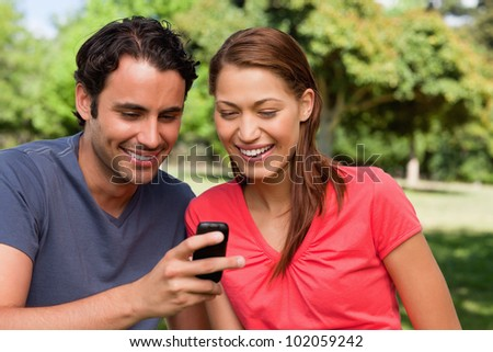 Two friends smiling as they are looking at something on a mobile phone while sitting in a bright grassland area - stock photo
