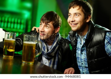 Two friends spending time at sport bar enthusiastic about the game - stock photo