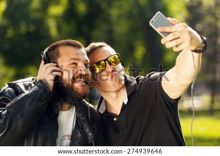 Two friends taking a selfie photo with mobile smart phone in nature, listening to music with headphones - stock photo