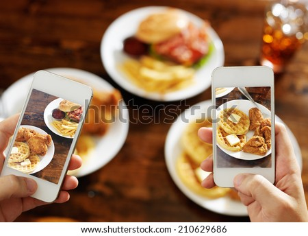 two friends taking photo of their food with smart phones - stock photo