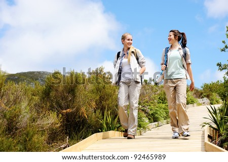 two friends walk outdoors along a wooden pathway - stock photo