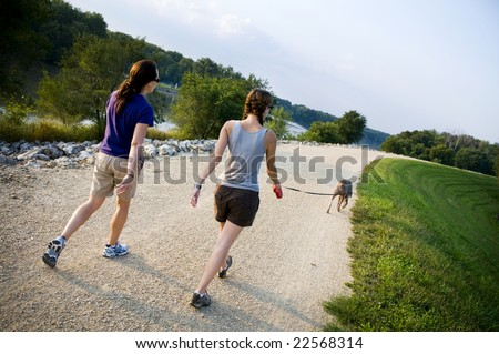 two friends walking a dog - stock photo