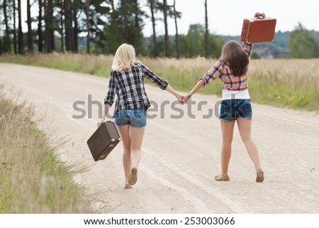 Two friends walking and holding hands in countryside - stock photo