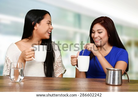 Two friends who are talking and drinking coffee - stock photo