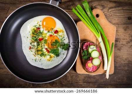two frying eggs with greens in pan on wooden table, with sausage sandwich - stock photo