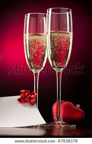 Two full glasses of champagne over red background