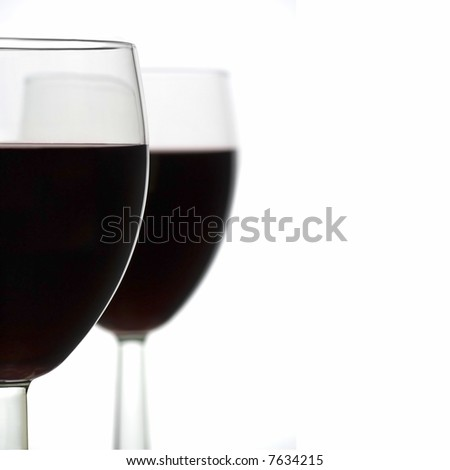 Two Full Wine Glasses with Focus on Closest Glass with Copy Space to Right - stock photo