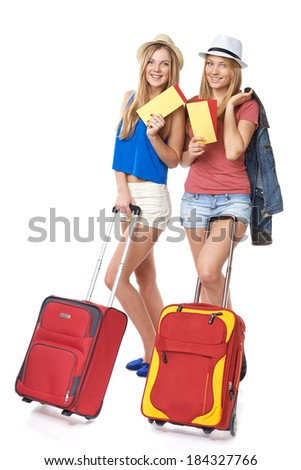 Two funky girls in shorts and straw hats standing with travel bag, holding tickets, isolated on white background - stock photo
