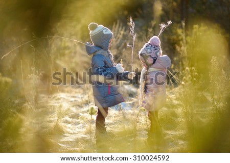 Two funny adorable little sisters having fun together in beautiful winter park - stock photo