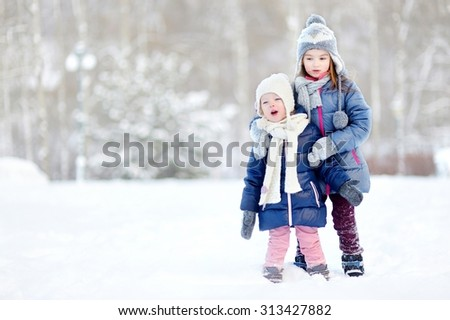 Two funny adorable little sisters having fun together in beautiful winter park during snowfall - stock photo